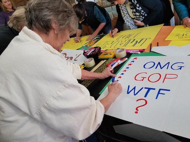 Sarah johnson creates a sign against the gop